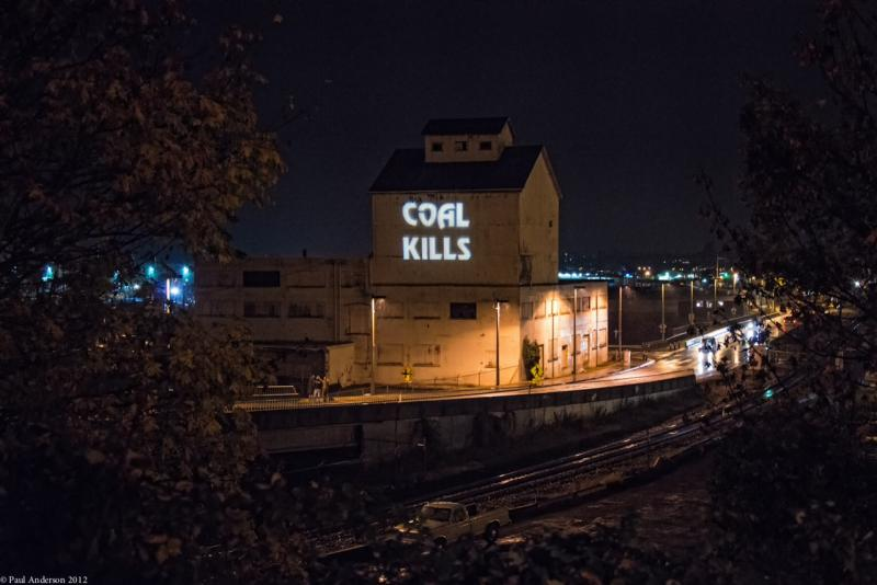 Coal shipment protesters projected words on the side of the old Granary Building in Bellingham's Old Town, along the waterfront last night. BNSF mainline tracks are in the foreground.