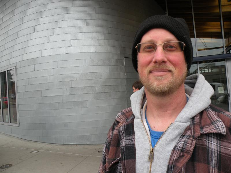 "Tracy Slatton lives in West Seattle, but submitted his ballot at the drop box outside the public library in Ballard. ""Most of it was just procrastination and making sure I got the vote in at the last minute,"" he says."