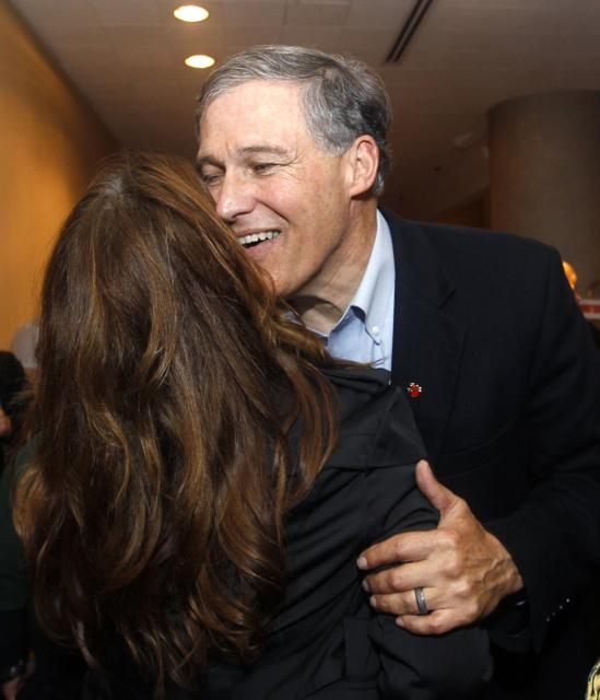 Democratic gubernatorial candidate Jay Inslee, right, embraces a supporter as Inslee walks through a hotel lobby before an election night party Tuesday in Seattle.