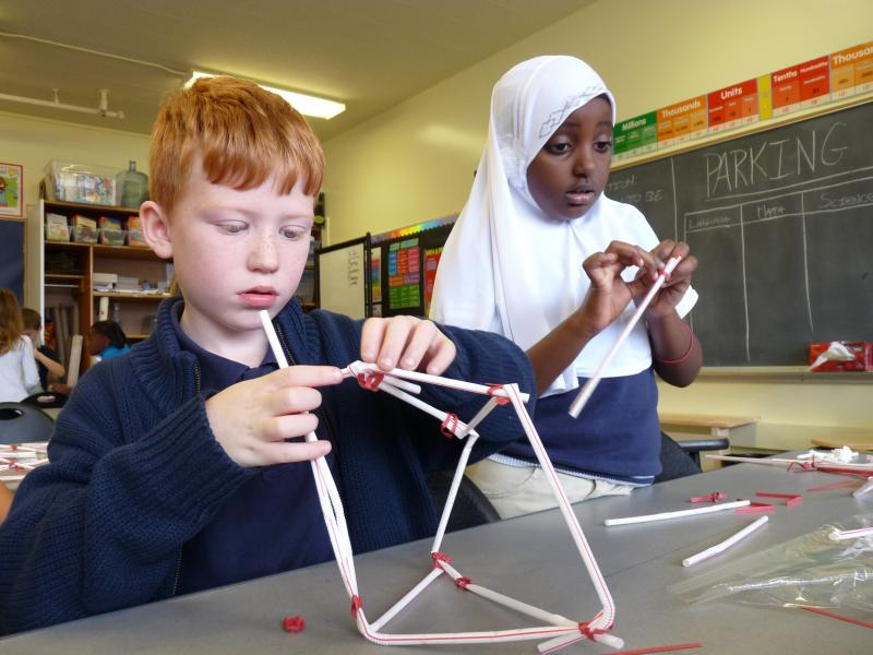 Students learn engineering principles by building towers out of straws and twist-ties.