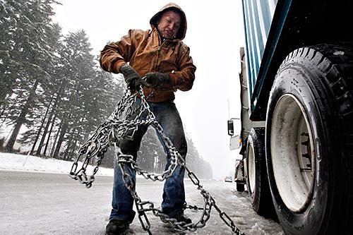 Manuel Garcia pulls the chains off of his semi-truck tires as quickly as he can as snow falls while parked at the eastbound milepost 34 exit of Interstate 90 earlier this year, near North Bend.