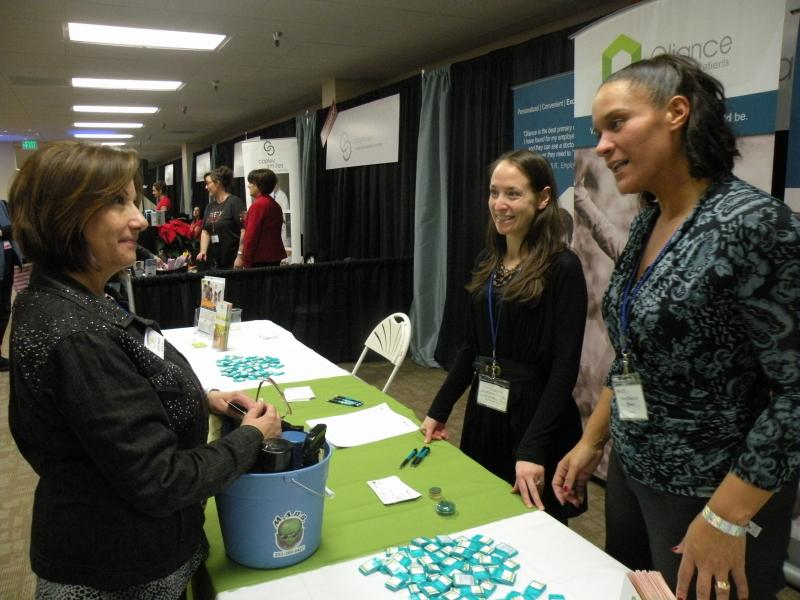 A BizX member inquires about supplementing her health care insurance at the booth of Qliance. A dental practice, massage therapists, catering companies and party rentals are among those in adjacent booths.