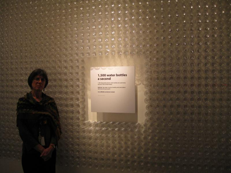 Exhibition Coordinator and writer Ruth Pelz with the wall of disposible water bottles.