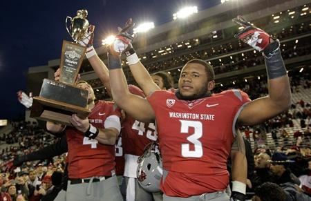 WSU's Carl Winston (3) celebrates winning the Apple Cup trophy with teammates on Nov. 23, 2012, in Pullman. Is that overtime victory a reason why sales for UW's bowl appearance are lagging?
