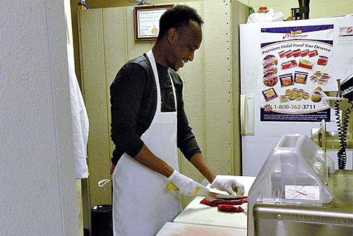 Owner Abdi Aden cuts halal meat at his store in Tukwila.