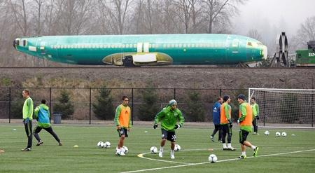 Sounders players take part in practice drills during MLS soccer training camp, Tuesday, Jan. 22, 2013, in Tukwila, Wash., as a Boeing 737 airplane fuselage passes by behind them on a railcar on the way to Boeing's assembly plant in Renton.