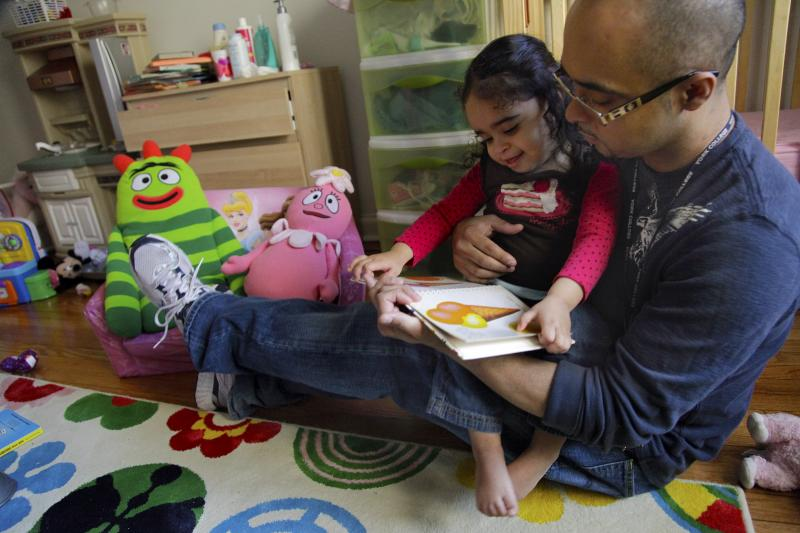 Christopher Astacio reads with his daughter Cristina, 2, recently diagnosed with a mild form of autism, in her bedroom on Wednesday, March 28, 2012 in New York.