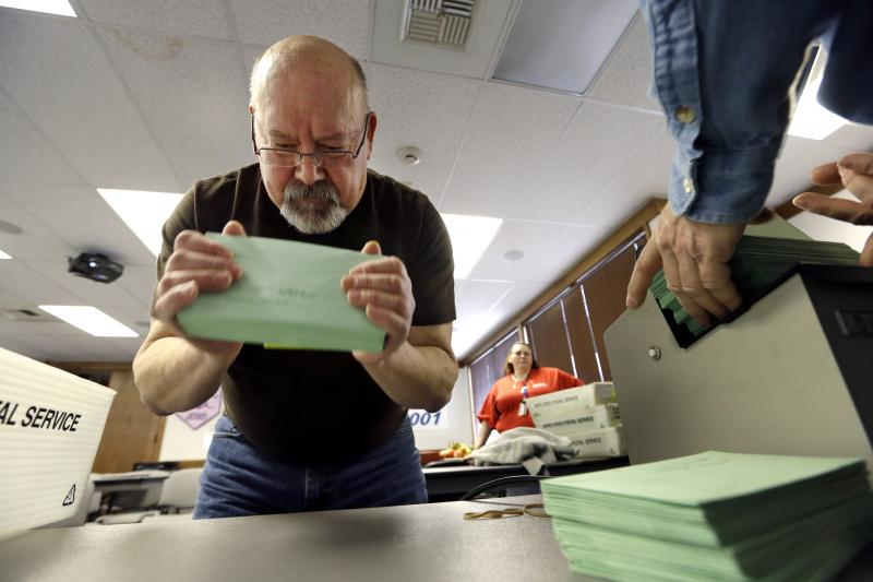 Boeing technical worker Richard Wichels stacks returned ballots before they go into a machine to be opened and readied for a count later in the day Monday, March 18, 2013, in Tukwila, Wash.