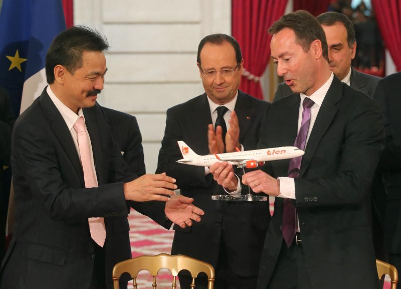 CEO of Airbus, French Fabrice Bregier, right, hands over an Airbus 320 model to CEO of Lion Air, Indonesian Rusdi Kirana, left, while France's President Francois Hollande stands behind at the Elysee Palace in Paris, March 18, 2013.