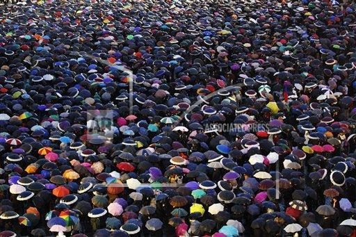 Visitors cover St. Peter's Square with their umbrellas as they wait for the election of a new pope by the cardinals in conclave in the Sistine Chapel at the Vatican, Wednesday, March 13, 2013.