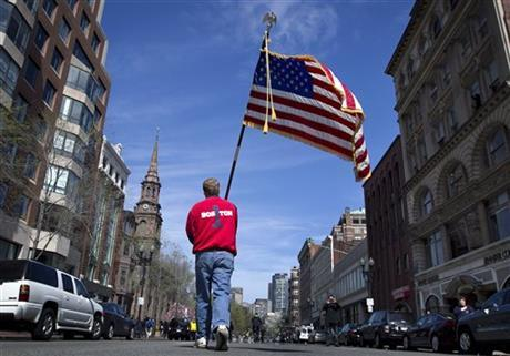 Lt. Mike Murphy of the Newton, Mass., fire dept., carries an American flag down the middle of Boylston Street after observing a moment of silence in honor of the victims of the bombing at the Boston Marathon near the race finish line, Monday, April 22, 20