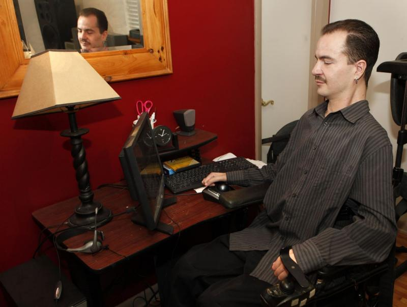 In this Dec. 6, 2012 file photo, Brandon Coats works on his computer at his home in Denver. Coats, a quadriplegic medical marijuana patient, was fired from his job in 2010 as a telephone operator at Dish Network after testing positive for marijuana.