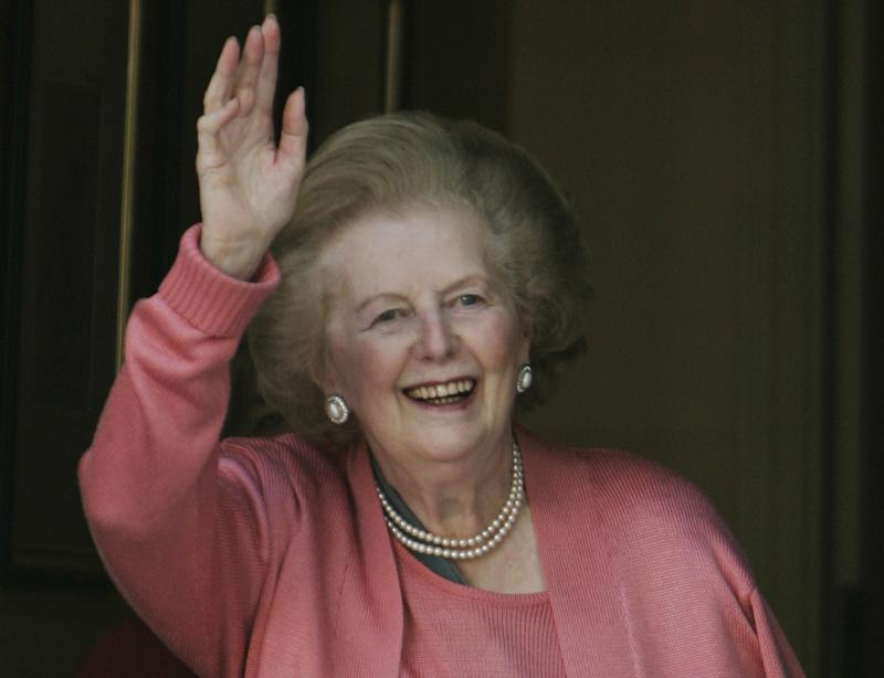 Former British Prime Minister Margaret Thatcher, gestures to members of the media as she stands on her house doorstep, following her return home from hospital, in central London, Monday June 29, 2009.