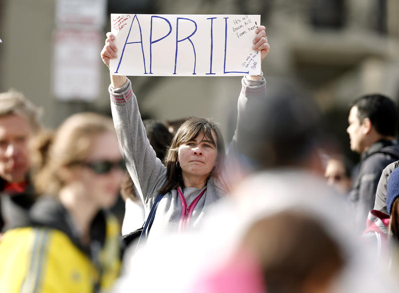 Justine Franco of Montpelier, Vt., holds up a sign near Copley Square in Boston looking for her missing friend, April, who was running in her first Boston Marathon Monday, April 15, 2013