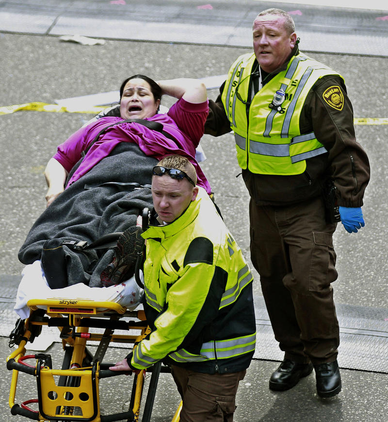 Medical workers aid an injured woman at the finish line of the 2013 Boston Marathon following two explosions there, Monday, April 15, 2013 in Boston