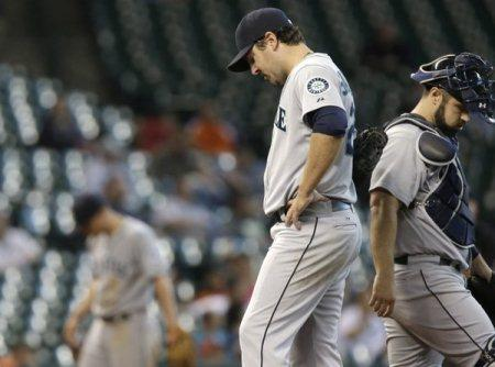 Mariners starting pitcher Joe Saunders, catcher Kelly Shoppach, right, and third baseman Kyle Seager hang their heads after Saunders gave up a double in Wednesday's game against the Astros in Houston.