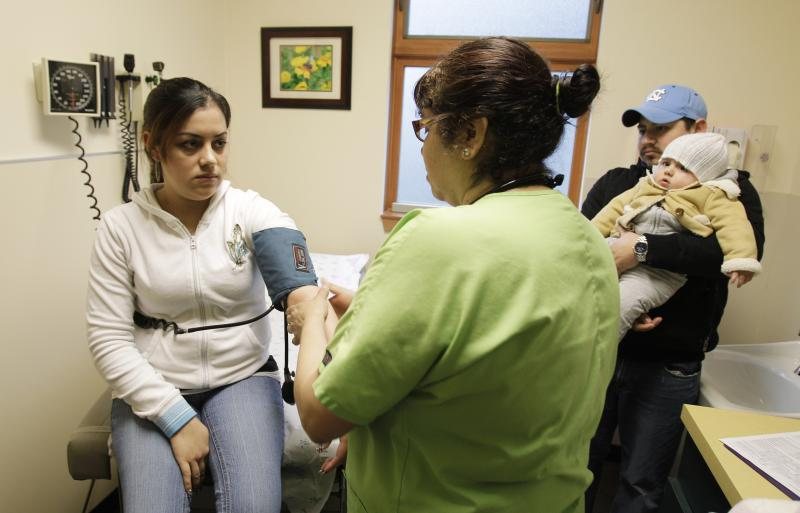 Veronica Rios, left, has her blood pressure taken by medical assistant Elizabeth Garza, center,as Rios' husband, Miguel Tamayo, and their daughter Paula look on at right, at the Country Doctor Community Clinic in Seattle, Friday, Feb. 4, 2011.