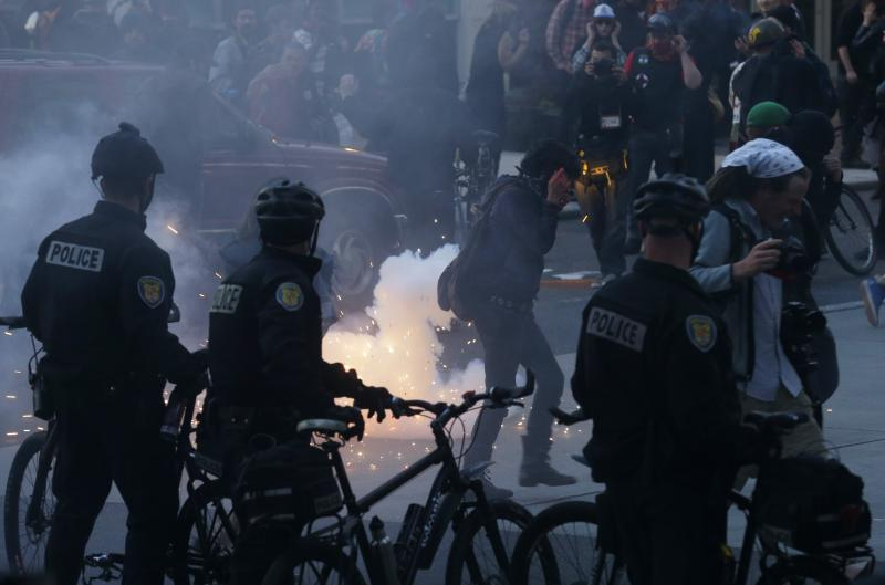 Protesters react as a firework is set off during May Day protests, Wednesday, May 1, 2013, in downtown Seattle.