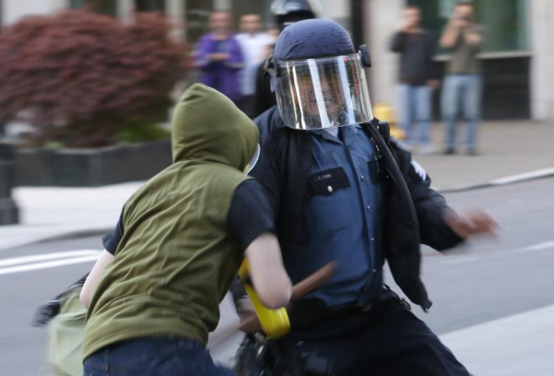A Seattle Police officer shoves his baton at a protester during a May Day march that began as an anti-capitalism protest and turned into demonstrators clashing with police, Wednesday, May 1, 2013, in downtown Seattle.