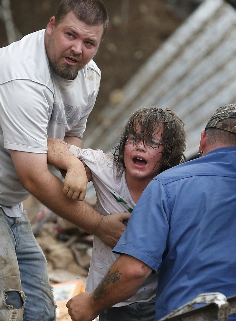 A child calls to his father after being pulled from the rubble of the Tower Plaza Elementary School following a tornado in Moore, Okla., Monday, May 20, 2013.