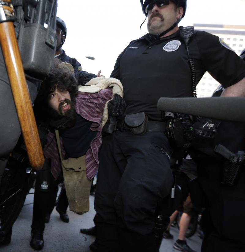 A protester who was arrested during a May Day march that began as an anti-capitalism protest and turned into demonstrators clashing with police is carried away by police Wednesday, May 1, 2013, in downtown Seattle.