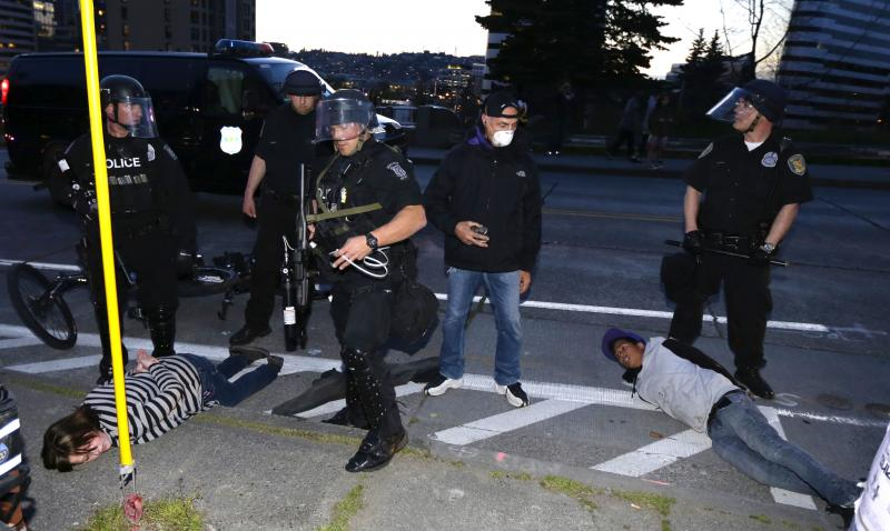 A bystander is seen snapping a photo of man being placed under arrest in Seattle on May Day 2013.