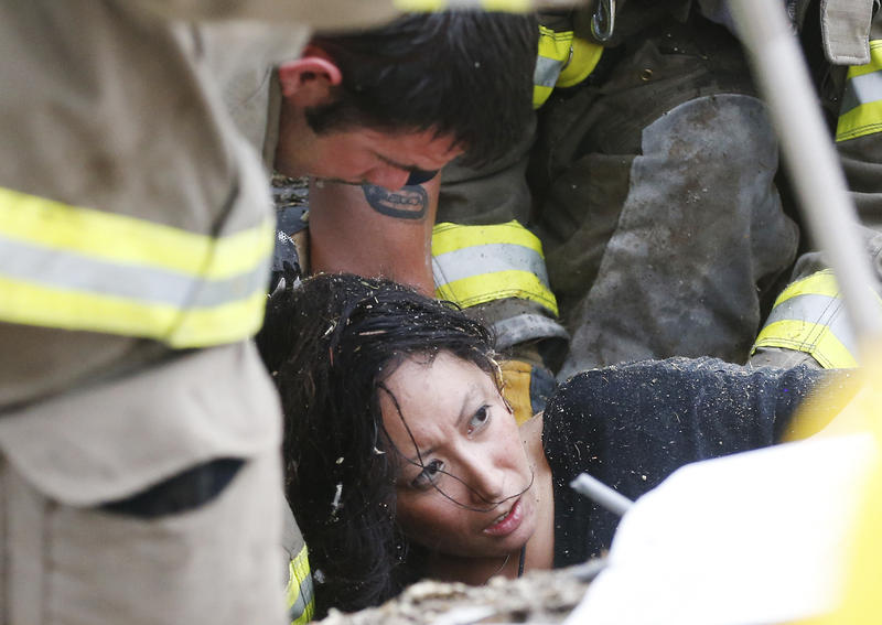 A woman is pulled out from under tornado debris at the Plaza Towers School in Moore, Okla., Monday, May 20, 2013.