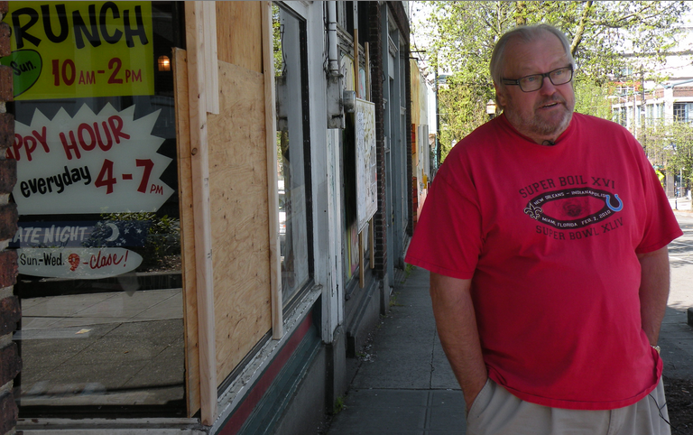 Don Stevens, owner of Bill's Off Broadway, stands next to his broken window.