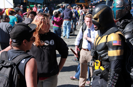 Phoenix Jones and a sidekick are seen talking to marchers on May Day 2013.