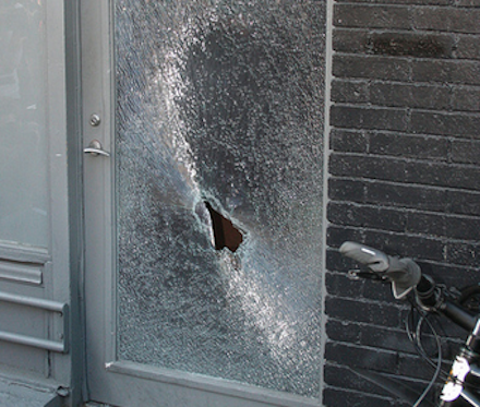 The smashed glass door of Sun Liquor is seen in this photo.