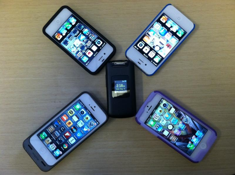 "Ashley Gross' ""dumb phone"" is seen next to her co-workers' smartphones in this photo."