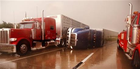 A truck squeezes past an overturned tractor-trailer on I-40 west of Banner Rd. Friday, May 31, 2013 in El Reno, Okla.