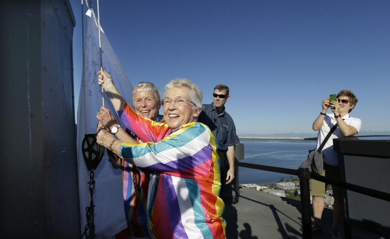 Jane Abbott Lighty, left, and her wife Pete-e Petersen turn toward photographers and supporters as they take a turn raising a giant marriage equality flag atop the Space Needle Sunday, June 30, 2013, in Seattle.