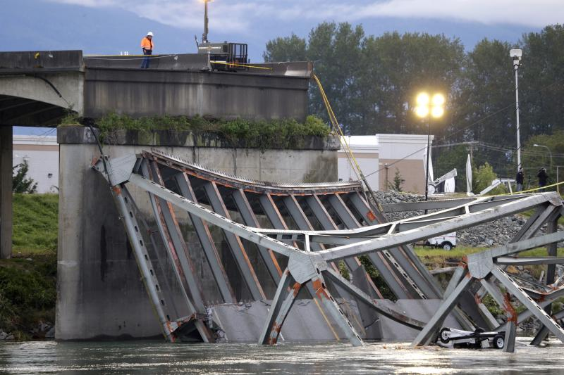 A worker looks at the collapsed portion of the Interstate 5 bridge at the Skagit River Friday, May 24, 2013, in Mount Vernon, Wash.