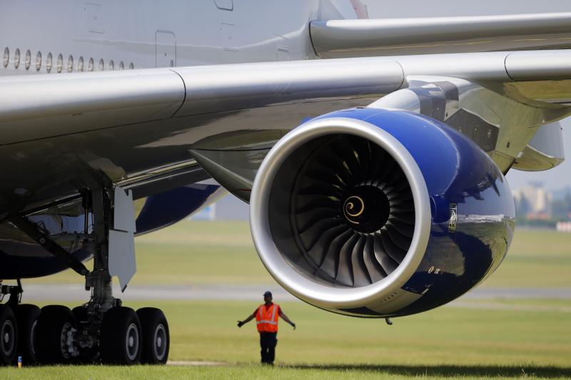 A ground controller is seen next of a Rolls Royce engine of a British Airways Airbus A380 during the first day of the 50th Paris Air Show at Le Bourget airport, north of Paris, Monday, June 17, 2013.
