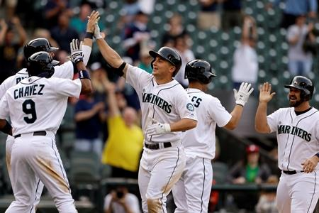 Kyle Seager, center, is greeted at home following his grand slam against the White Sox in the 14th inning to tie a baseball game on Wednesday at Safeco Field.