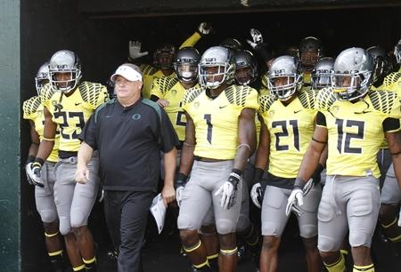 In this 2012 file photo, Oregon football coach Chip Kelly walks out of the tunnel with his team before their game against Fresno State in Eugene, Ore.