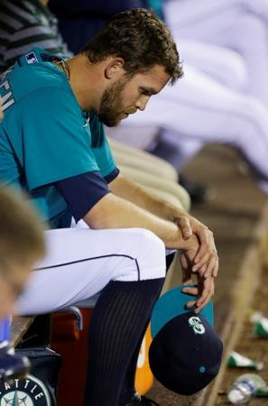 Mariners closer Tom Wilhelmsen sits in the dugout after blowing 1-0 lead in 9th inning against the Astros Wednesday. Houston won 6-1.