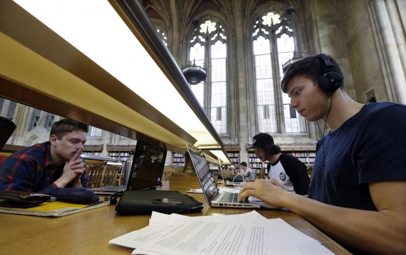 FILE - In this photo taken April 26, 2013, University of Washington students Benjamin Ferschli, left, Oscar Haavardsholm and Nicholas McMillan study in Suzzallo Library at the school in Seattle.