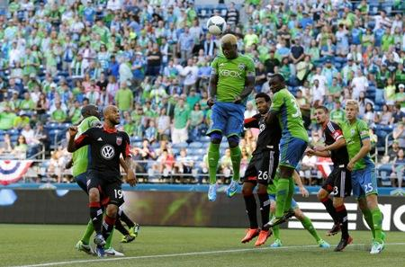 The Sounders' Eddie Johnson, center, heads the ball during a match against D.C. United on July 3 in Seattle.