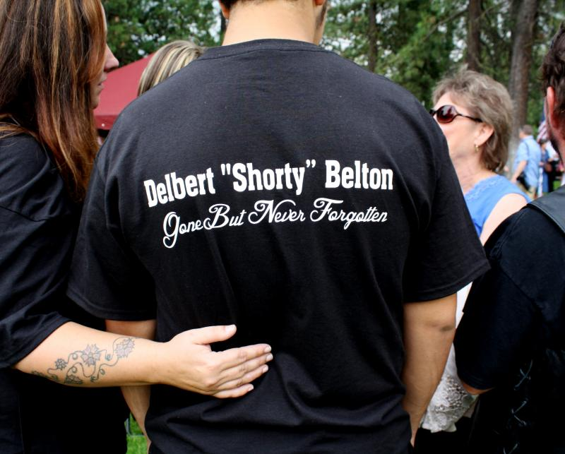 Michael Brown, 16, stands with his mom, Kim Brown, at the memorial for Delbert Belton. The Browns knew Belton for years and had custom T-shirts made in his honor.