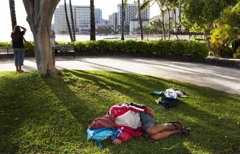 FILE - In this Friday, May 13, 2011 file photo, a man sleeps on the ground near Waikiki Beach, in Honolulu.