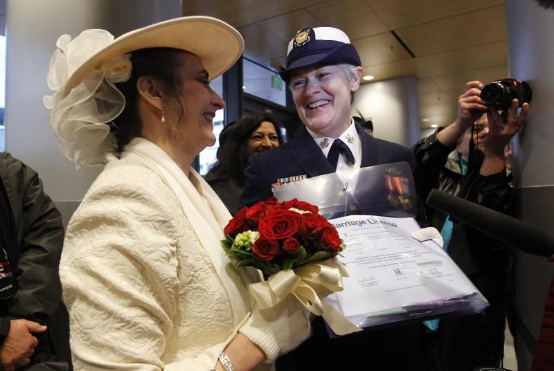 Retired U.S. Coast Guard Petty Officer 1st Class Nancy Monahan, right, wears her dress uniform as she holds her marriage license and stands with her soon-to-be bride Deb Needham as they wait at Seattle City Hall, Sunday, Dec. 9, 2012, in Seattle.