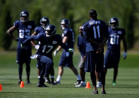 Injured Seahawks wide receiver Percy Harvin (11) can only stand and watch as other receivers go through practice drills during training camp Sat., July 27, in Renton.