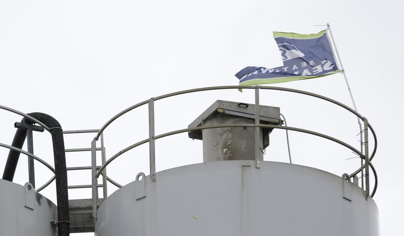 A wind-damaged Seattle Seahawks flag flies Monday, Sept. 30, 2013 at EnCon Washington in Puyallup, Wash.