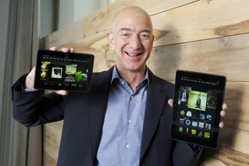 In this image distributed on Tuesday, Sept. 24, 2013, Amazon.com Founder and CEO Jeff Bezos introduces the all-new Kindle Fire HDX 8.9'', right, and Kindle Fire HDX 7'' tablet in Seattle.
