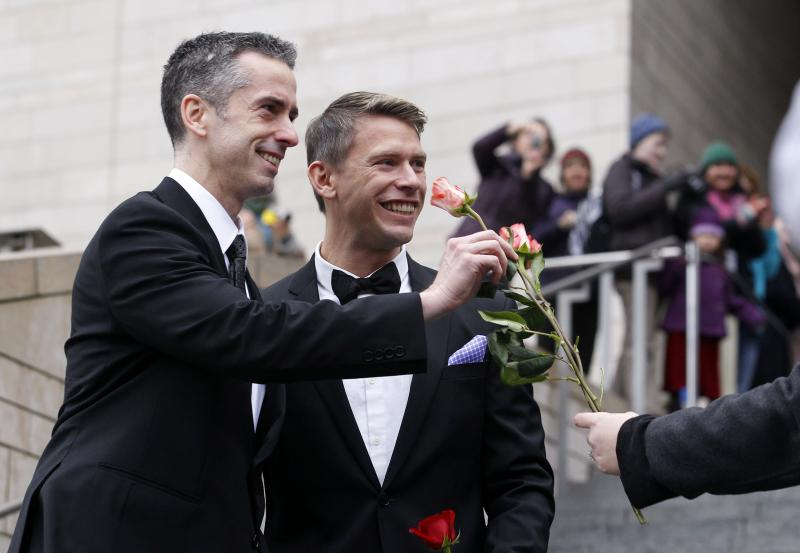 Dan Savage, left, and his husband Terry Miller are handed flowers after their wedding at Seattle City Hall, Sunday, Dec. 9, 2012.