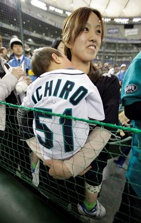 A mother in Tokyo holds her two-year-old son wearing a jersey of former Mariner Ichiro Suzuki as she watches the team's practice prior to a game in Tokyo between the Mariners and the A's in March 2012. Yamauchi was integral in bringing Ichiro to Seattle.