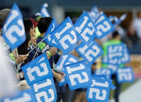 "Seahawks ""12th Man"" flags are waved before a preseason game against the Denver Broncos on Aug. 17, 2013, in Seattle."