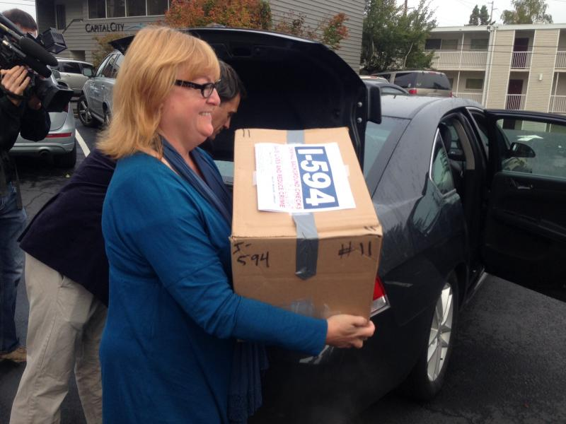 Cheryl Stumbo, a survivor of the 2006 Seattle Jewish Federation shooting carries a box of Initiative 594 petitions. Stumbo is the sponsor of the measure to require universal background checks for gun sales in Washington.